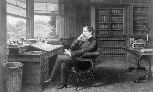 Vieille photographie en noir et blanc de Charles Dickens assis à son bureau, l'air pensif