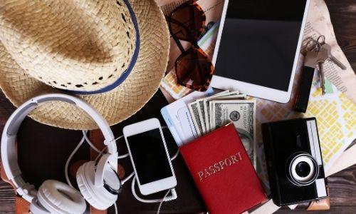 accessoires pour partir en vacances étalés sur un lit : casque, téléphone, passeport, appareil photo, billets, tablette, lunettes de soleil
