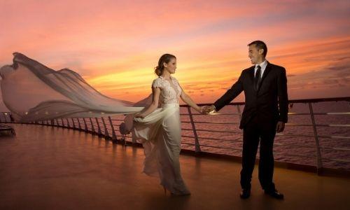 couple qui se regardent et se tiennent la main, habillés de manière classe avec la robe de la dame qui prend le vent, sur le pont d'un bateau