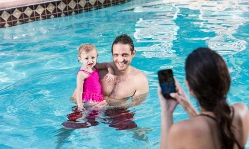 jeune femme de dos qui tient dans ses mains un téléphone pour prendre son homme et sa petite fille en photo dans la piscine, eux sont en face d'elle et sourient