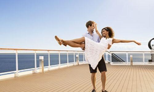 jeune couple sur le pont d'un bateau, l'homme porte sa conjointe dans les bras, qui elle tend et les jambes et les bras en lui souriant