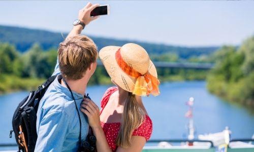 jeune couple de dos, l'homme tend son bras avec son téléphone dans la main pour prendre un selfie de lui et sa compagne