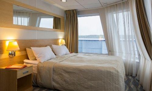 cabine d'un bateau avec un lit double au centre et un balcon en arrière-plan