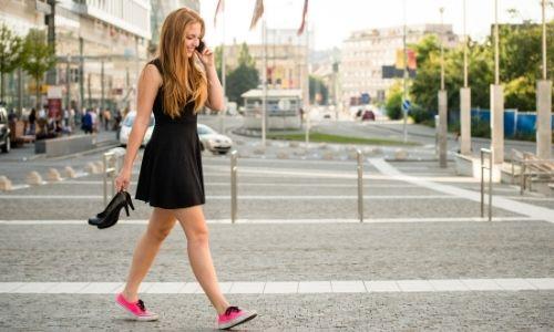 jeune femme au téléphone, marchant dans la rue, qui porte à la main ses talons qu'elle a troqué contre des baskets confortables aux pieds