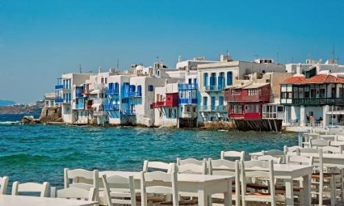 Maisons construites au bord de l'eau, comme sur le fil de l'eau en arrière-plan et tables avec chaises blanches au premier plan