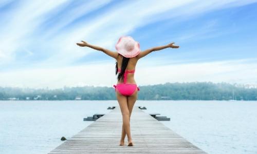 Femme de dos sur un ponton, en maillot de bain et chapeau, levant les bras en l'air
