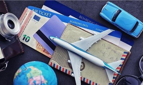 documents essentiels pour un voyage : billets, appareil photo, ticket d'avion, port monnaie, etc