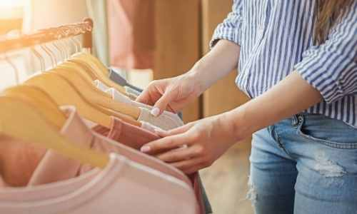 jeune femme qui choisit un pull dans sa penderie pleine de vêtements sur cintre