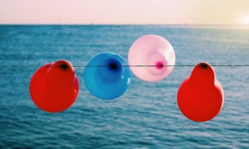 Ballons couleurs bleu rouge et blanc suspendus à un fil face à la mer