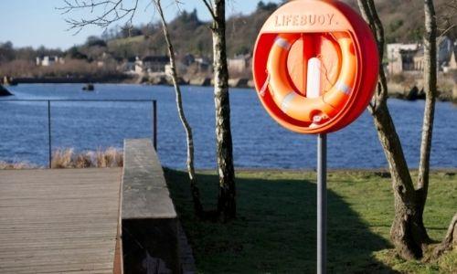 Bord d'une rivière avec une bouée de sécurité orange à droite d'un ponton en bois