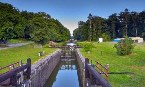 Ecluse d'un canal entourée de d'arbres et de pelouse verdoyants
