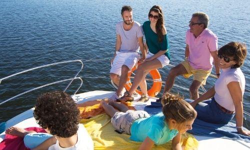 Famille sur le devant d'un bateau sans permis en pleine rivière