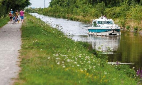 Famille qui se promène le long d'un canal, sur lequel on retrouve une pénichette
