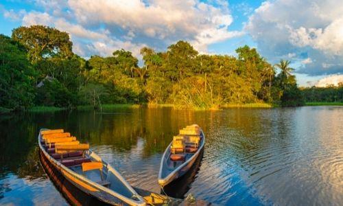 Deux barques sur le fleuve de l'Amazone lors de la golden hour
