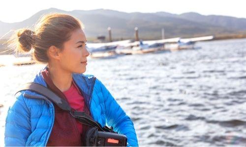 Jeune femme qui regarde l'horizon sur un bateau de croisière, équipée pour une excursion
