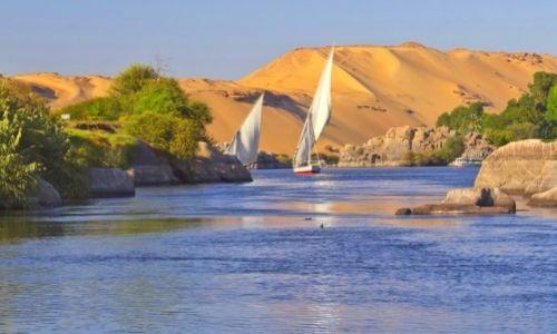 Dunes de sable en arrière-plan, avec des bateaux qui naviguent sur le Nil au second plan