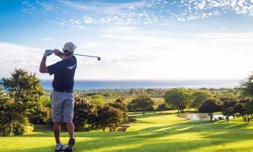 Joueur de golf, de dos, sur son parcours, face à la mer