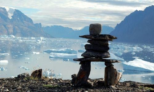 paysage d'antarctique avec les montagnes enneigées au loin et des blocs de glace sur l'eau