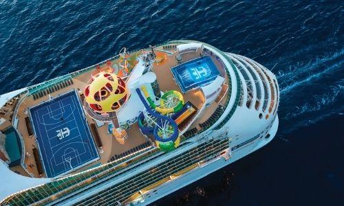 vu d'une partie d'un bateau de croisière, de haut avec la vue sur un terrain multisport, un toboggan en spirale, un simulateur de surf, etc.