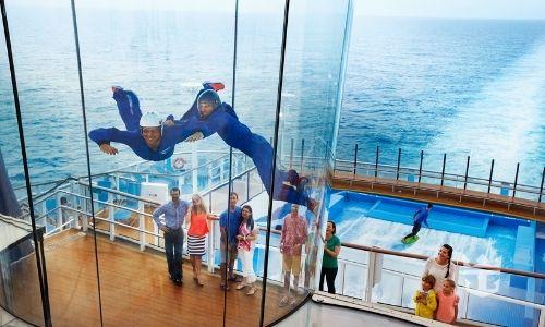 deux personnes dans un tube en combinaison qui profitent de la simulation d'une chute libre à bord d'un bateau de croisière, observées par des personnes amusées de la situation.