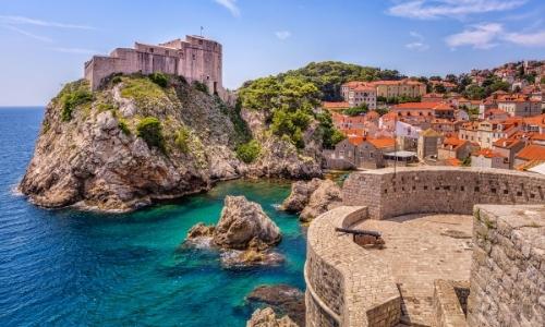 Vue sur Dubrovnik, bord de mer avec rochers, et remparts, avec château en hauteur