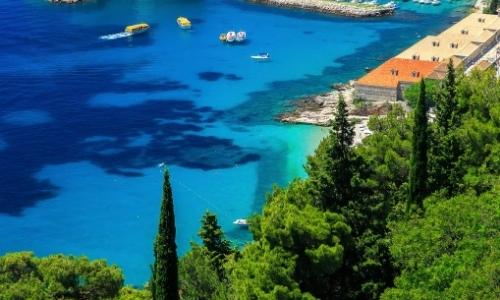 Vue aérienne sur les eaux cristallines de Dubrovnik avec bateaux, végétation en bord de ner