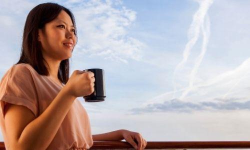 jeune femme qui regarde l'horizon à la barre d'un bateau, une tasse de café à la main