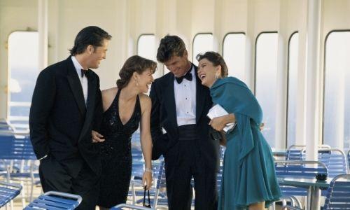 deux couples qui rigolent entre eux, vêtus de tenues très chics, à bord d'un bateau