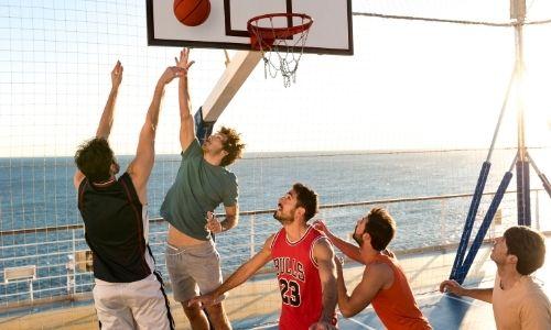 cinq jeunes garçons qui jouent au basketball sur un terrain multisport d'une croisière, l'un est en train de shooter pendant qu'un autre défend sous le regard des trois autres