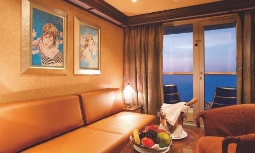 Intérieur d'une cabine avec vue mer, canapé, fauteuil, tableaux sur le mur