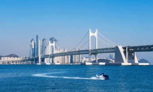 vue sur la mer avec au loin un grand pont et des buildings