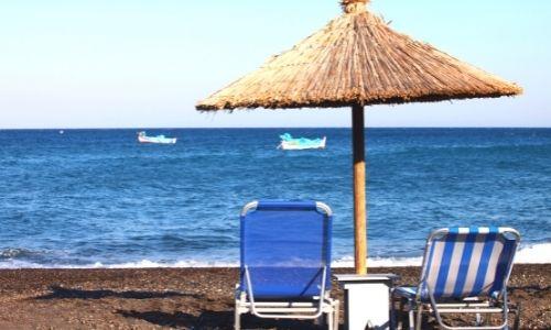 plage de Santorin avec un transat et un parasol en osier