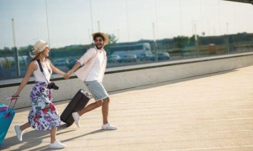 couple qui court avec leurs valises à la main dans un aéroport