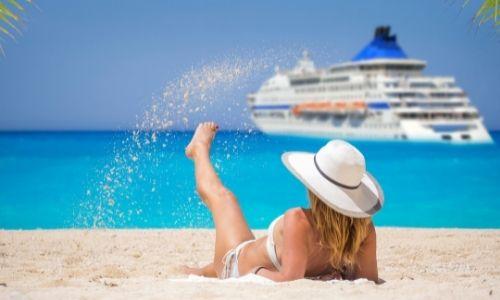 jeune femme sur la plage qui jette du sable avec son pied, on aperçoit un bateau de croisière au loin