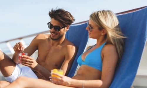 Un couple sur des transats, moments farniente sur le pont du bateau en maillot de bain