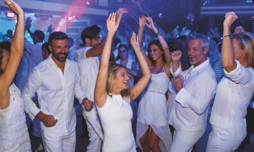 Groupe de personnes dansant à une soirée blanche, avec tenues blanches