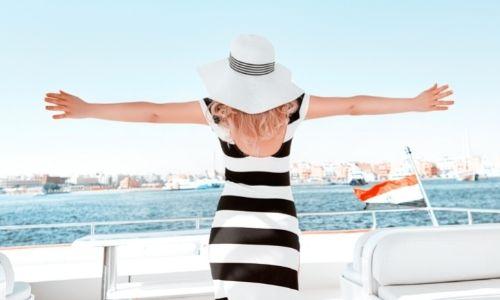Femme de dos sur un bateau qui tend les bras sur les côtés comme un air de liberté