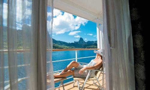 Une cabine du Paul Gauguin donnant vue sur une île polynésienne