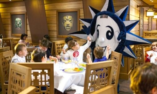 Des enfants qui mangent entre eux et la mascotte MSC