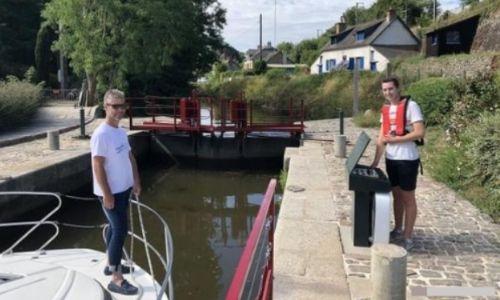 Un touriste de plaisance (sur son bateau sans permis) est aidé par un éclusier