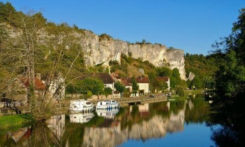 Village de Merry-sur-Yonne et le rocher de Saussois, des bateaux sont amarrés à la berge.