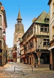 Les ruelles pavées et maisons à colombages laissent entrevoir la tour de l'horloge de Dinan