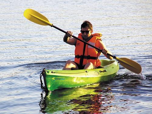 Un homme portant un gilet de sauvetage fait du canoë kayak sur une étendue d'eau
