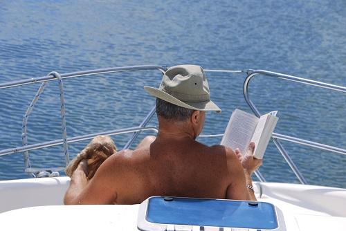 Un homme, sur son bateau et muni d'un chapeau, lit un livre et bronze avec son chien