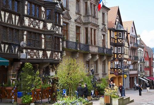 Rangée de maisons alsaciennes à colombages, des touristes les observent depuis la rue piétonne