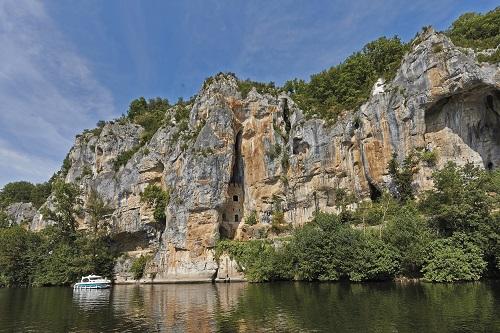 Un bateau de la compagnie Nicols vogue sur le Lot, l'immense falaise en arrière plan couvre quasiment toute la photo