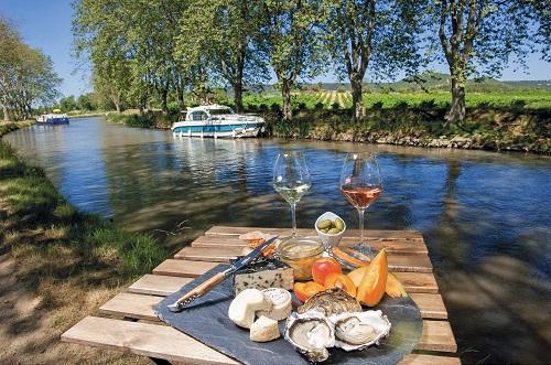 Table de pique nique terroir (fromages, huîtres, fruits et verres de vin) devant le canal du Midi et ses platanes. Un bateau de location est amarré sur une berge.