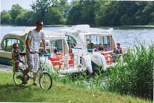 Un père et son fils font une balade à vélo tandis que le reste de la famille est sur deux bateaux au second plan