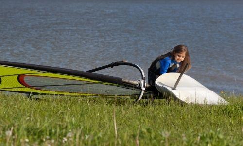 Jeune fille apprend à faire de la planche à voile sur l'étang de Thau