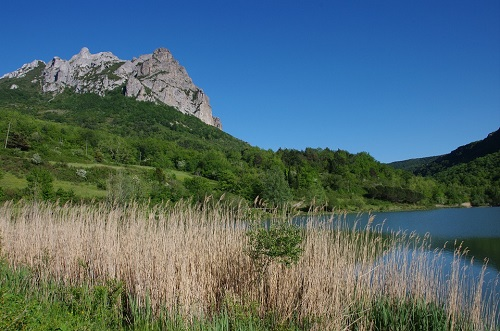 Le bord du lac affleure la montagne de Bugarach baigné dans un ciel bleu